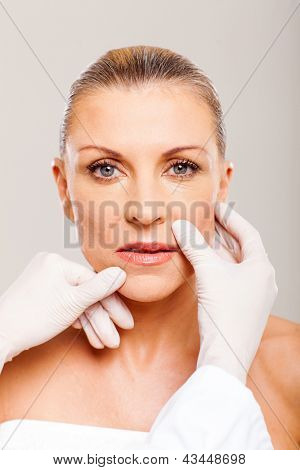 doctor checking middle aged woman lips before plastic surgery