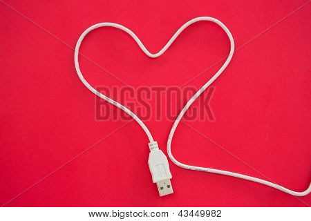 Cable USB in form of heart on red background