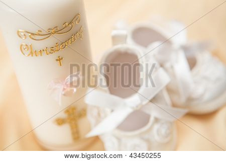 Baptism candle and baby booties on yellow blanket