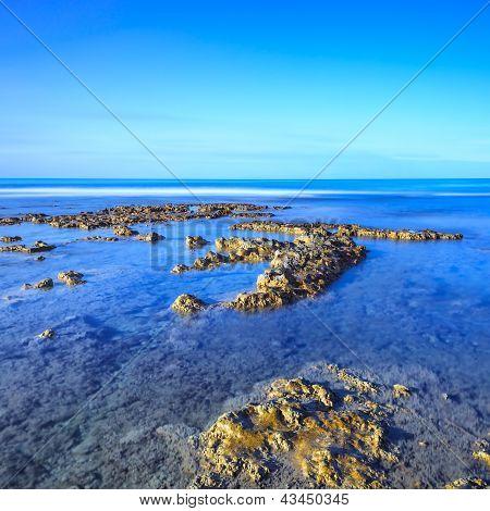 Rocks In A Blue Ocean Under Clear Sky On Sunrise.