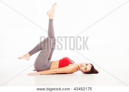 Beautiful woman working out lying on her back on the floor with her legs raised in the air on a white background