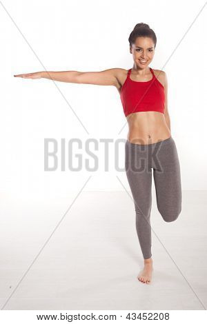 Woman working out at a gym balancing on one foot with her arms raised to the side while smiling at the camera