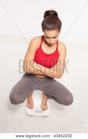 Barefoot young woman crouched on her bathroom scale reading her weight on the display with a look of disapproval