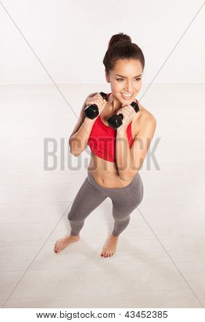 High angle view of a smiling attractive young woman working out with dumbbells