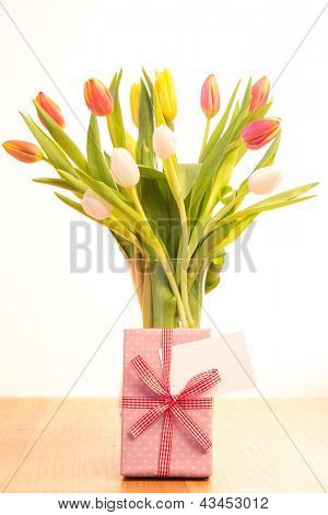 Vase of pink white and yellow tulips on wooden table with gift and blank card