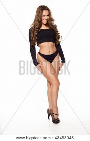 Sexy young woman in black underwear, with long curly brown hair, posing for the camer
