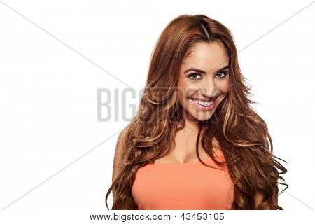 Beautiful joyful young woman with long curly hair wearing an apricot coloured top and smiling at the camer