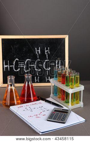 Tubos de ensaio com líquidos coloridos e fórmulas sobre fundo cinza