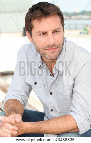 pensive man sat riverside