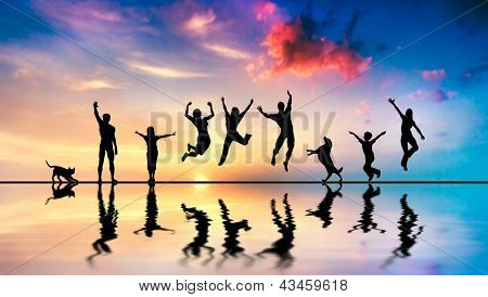 Happy group of friends, family with dog and cat jumping together at sunset, water reflection