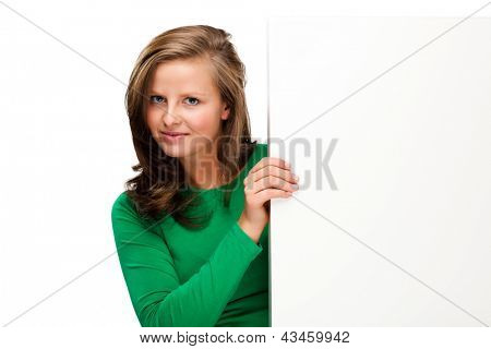 Young attractive woman behind empty board isolated on white background
