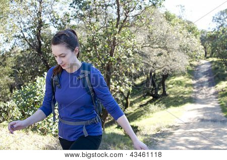 Close up woman hiking up a hill, empty space right