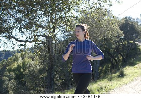 Centered close up of woman jogging outside in a blue shirt