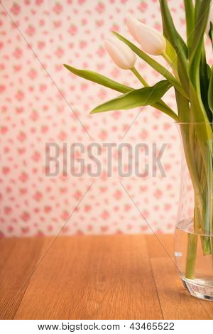 Vase of tulips on wooden table with wallpaper background