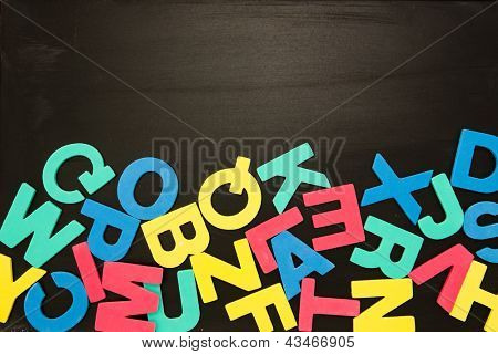 Alphabet magnets in a jumble on bottom of blackboard with copy space