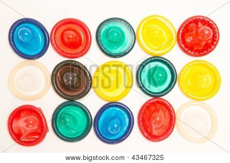 Many different coloured condoms on white background
