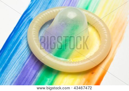 Condom on gay pride rainbow brush stroke