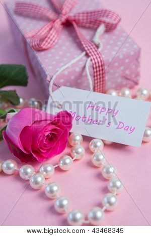 Pink rose with gift and string of pearls for mothers day on pink surface