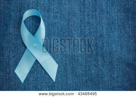 Blue ribbon for prostate cancer awareness on blue demin with copyspace