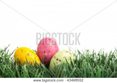 Small easter eggs nestled in the grass on white background