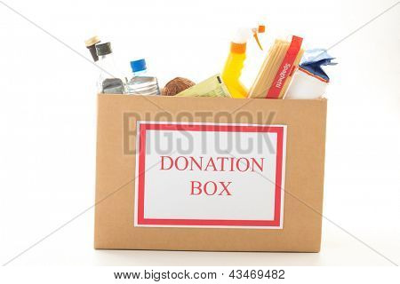 Cardboard donation box with houseware product and food on white background