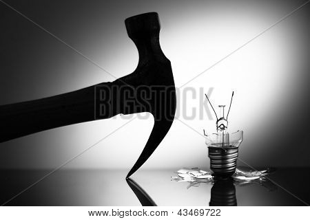 Clear light bulb broken by hammer in black and white