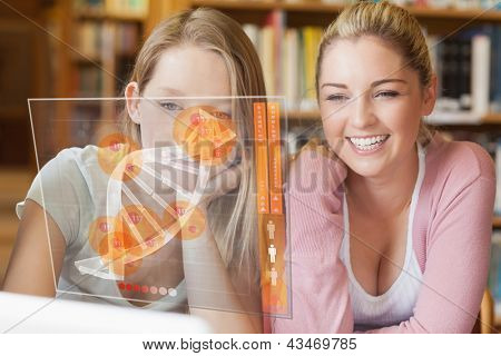 Two smiling students looking at laptop and futuristic interface with DNA