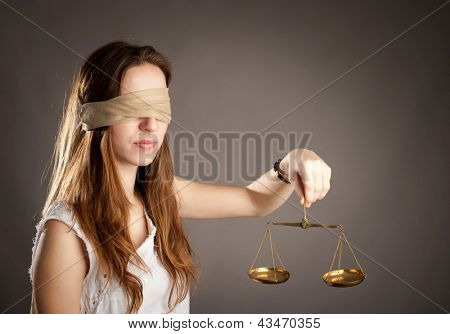 woman with covered eyes holding a justice scale