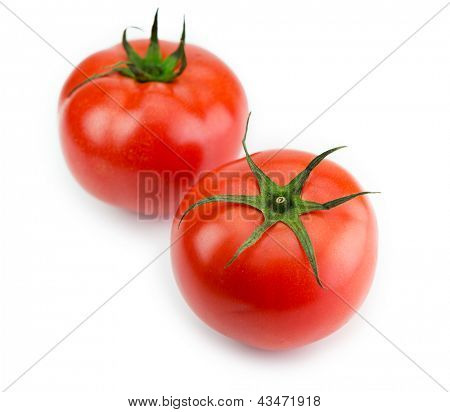 Two red ripe tomato with long sepal leaves still intact.Isolated on white.