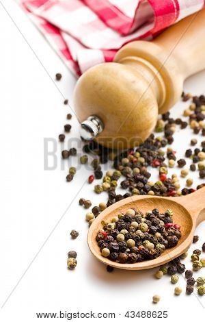 pepper and wooden pepper mill on white background