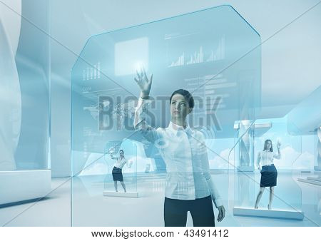 Future teamwork concept. Future technology touchscreen interface. Girl touching screen interface in hi-tech interior. Business lady pressing virtual button in futuristic office.