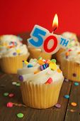 image of 50th  - Delicious cupcake with 50th candle on top and 49 other cakes in background - JPG