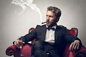 stock photo of mafia  - handsome boss sitting on the armchair smokes cigar - JPG