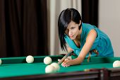 Young girl playing billiard. Spending free time on gambling