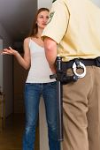 stock photo of interrogation  - Police officer at front door of home interrogating a woman or witness regarding a police investigation - JPG