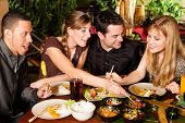 stock photo of chinese restaurant  - Young people eating in a Thai restaurant - JPG