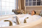 stock photo of bubble bath  - A young woman taking a relaxing bubble bath - JPG