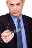 Businessman offering his glasses