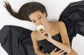 stock photo of carnal  - sweet portrait of a young and cute brunette laying down kissing a white rose - JPG