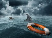 stock photo of survival  - Illustration of a lifebuoy adrift in the ocean surrounded by hungry sharks - JPG