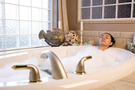image of hot water  - A young woman taking a relaxing bubble bath - JPG