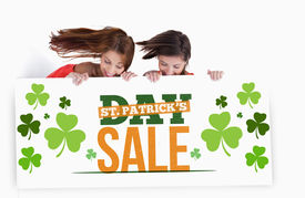 image of st patty  - Girls holding placard with st patricks day sale text in green white and orange with shamrocks - JPG