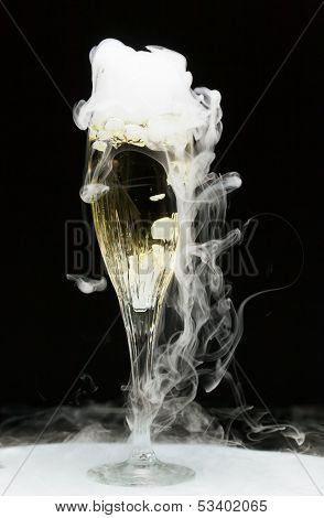 champagne flute with ice vapor, black background