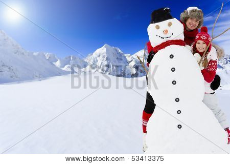 Ski, skier, sun and winter fun - skiers with snowman enjoying winter holidays