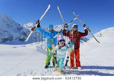 Ski, skiers, sun and fun - family enjoying winter vacation