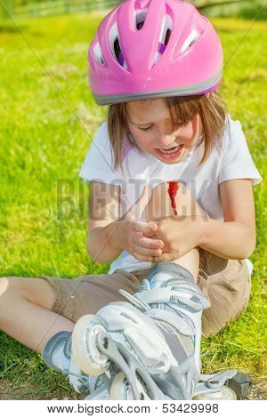 Preschool roller skate beginner looking at her bleeding knee.