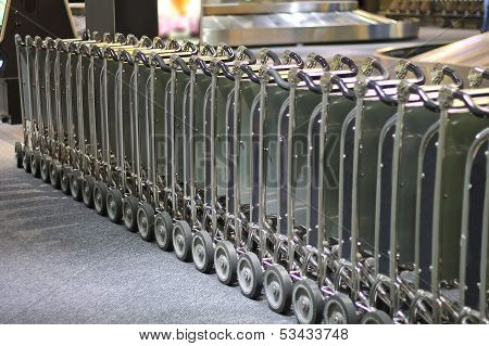 Row Of Luggage Carts At The Airport Arrival Hall