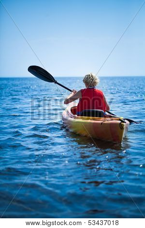 Woman Wearing A Safety Vest Heading Out To Sea Alone