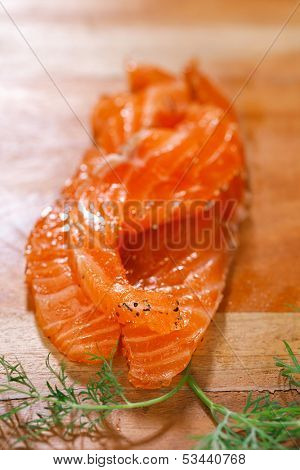 smocked salmon slices and dill, homemade, with spice on wooden board