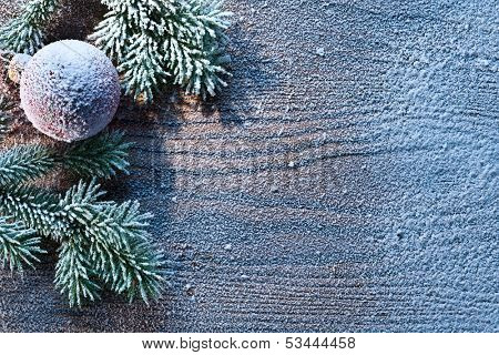 Christmas decoration with fir and baubles over wooden background.
